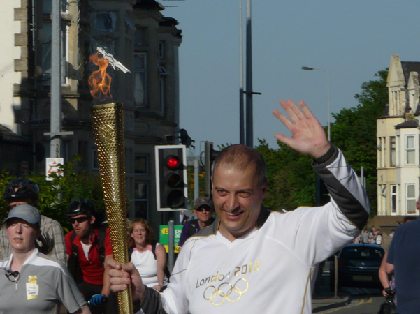 David Meek carries the Olympic Torch through Newport Road within yards of having a pint at the Club.